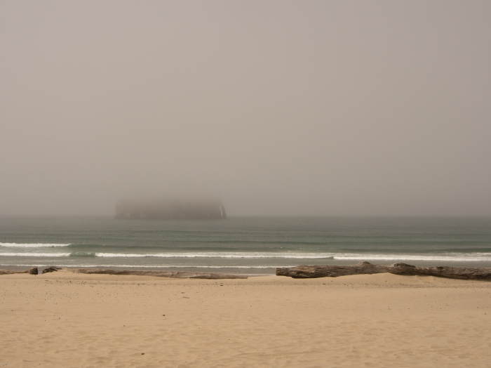 Haystack Rock slowly disappears from view at Cape Kiwanda